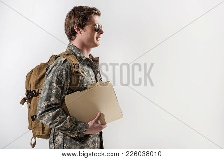 Happy Young Male Soldier Smiling And Holding Document Case In Hand. He Is Wearing Spectacles And Bac