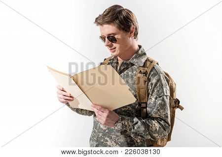Concentrated Military Guy Looking At Document Case In His Hands And Reading Information. He Is Havin