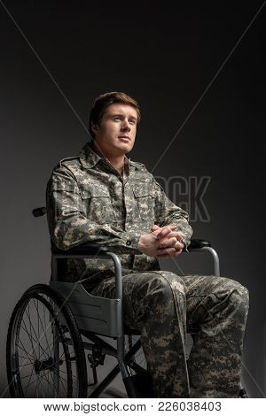 Portrait Of Hopeful Handicapped Young Veteran Sitting In Invalid Chair. He Is Looking Up With Belief