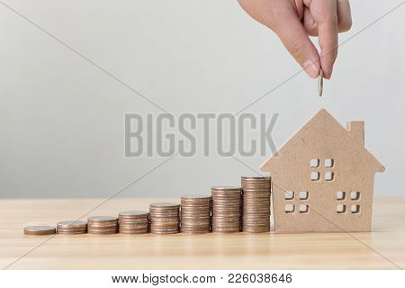 Property Investment And House Mortgage Financial Concept, Hand Putting Money Coin Stack With Wooden