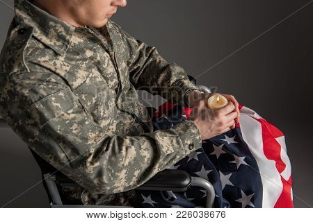 Top View Of Handicapped Veteran Having Candle And Flag In His Hands. He Is Sitting In Wheelchair And