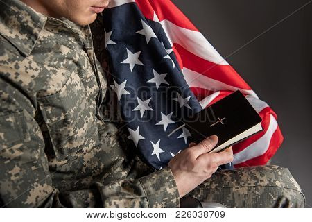 Top View Of Male Veteran Holding Flag And The Bible In His Hands. He Is Wearing Military Uniform. Is