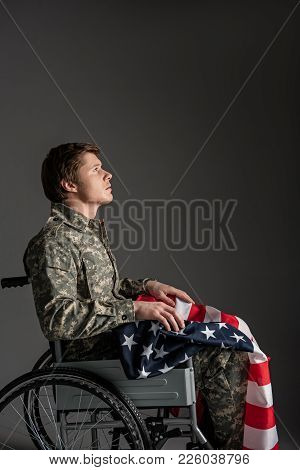 Sorrowful Paralyzed Soldier Sitting In Wheelchair With Sad Look. He Is Looking Up And Having A Flag