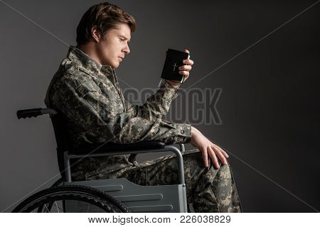 Despondent Handicapped Veteran Sitting In Wheelchair. He Is Holding The Book With Sad Look. Isolated