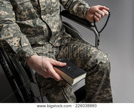 Top View Close Up Of Handicapped Soldier Holding Beads And The Bible In His Hands. He Is Sitting In