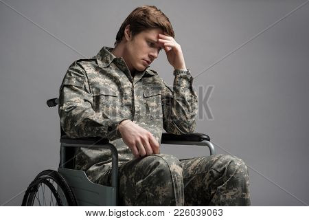 Hopeless Young Military Man Sitting In Wheelchair. He Is Looking Down With Frustrated Look And Propp