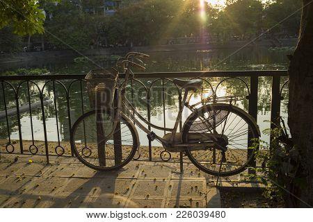 Old Bike On Urban Pavement Under Afternoon Bright Sunlight