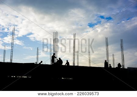 Hdr Effect Of Silhouette Workers Working At Building Construction Side At Sunset Time
