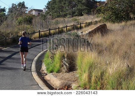 San Marcos, California - February 4, 2018: One Woman Jogging On Paved Trail That Curves Uphill, Foun