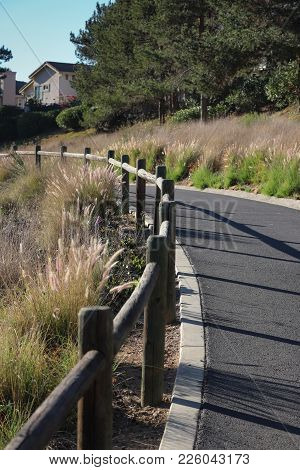 Paved Urban Hiking Trail With Wooden Railing Casting Shadows On Pavement, Curving Uphill, Fountain G