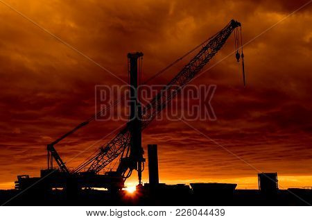 Crane And A Drill Standing Tall At Sunset.