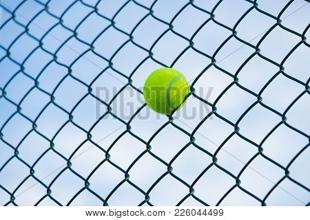 Tennis Ball On Metal Wire Against Sky. Concept Of Tennis Protection Equipment