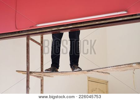 Worker Legs On Easy Breakable Ladder. Concept Of Painting Worker And Dangerous Work