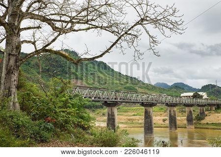 Central Highland Tay Nguyen Scene In Vietnam With Old Bridge Over Almost Dry River And High Tree On
