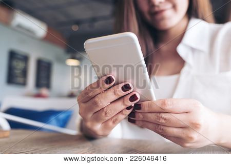 Closeup Image Of A Beautiful Asian Woman Holding , Using And Looking At Smart Phone In Modern Cafe