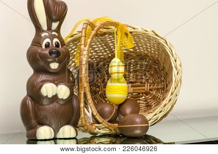 Chocolate Easter bunny eggs and sweets in Easter basket. Chocolate eggs with white Easter Bunny on egg. White Chocolate Easter bunny with chocolate eggs and sweets in Easter basket. Easter bunny chocolate egg hunt. Easter Bunny card.