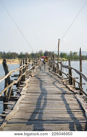 Ong Cop Wooden Bridge, The Longest Wooden Bridge In Vietnam. Focus On Heavy Loaded Motorbike