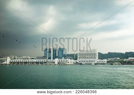 River Landscape With River, High Building On River Bank, Cable Car Station And Black Clouds Before R