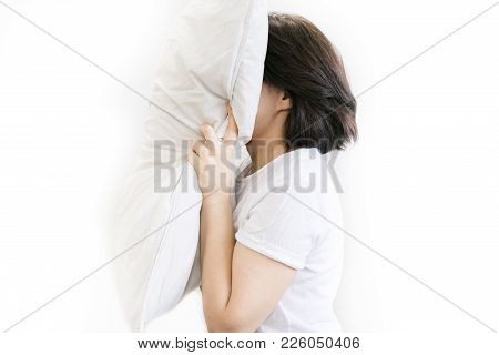 Angry Woman With Insomnia Yelling And Holding Pillows While Sitting In Bed