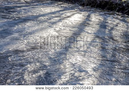 Complete Slippery And Frozen Path With Footprints And Shadows Of The Deep Sun