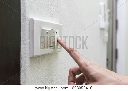 Woman Turning Off Light Switch In A Home