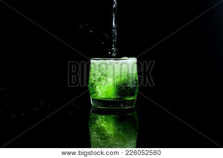 Fresh Green Italian Soda Drink With Splashing And Crushed Ice In Freeze Motion Into Glass On Black B