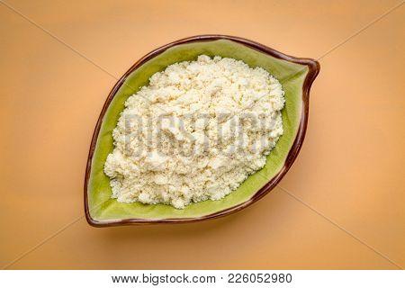 leaf lshpaed bowl of whey protein powder against beige background
