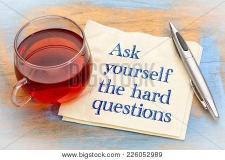 Ask yourself hard questions inspirational reminder - handwriting on a napkin with a cup of tea