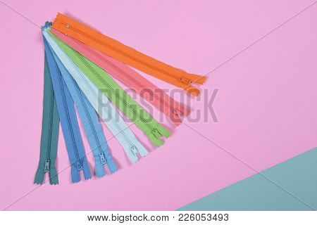 Flat Lay Of Colored Zipper For Sewing On Pink Background, Sewing And Needlework Concept.