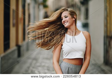 Happy Young Woman With Moving Hair In Urban Background.