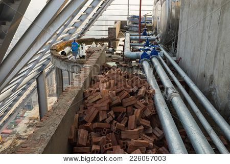 Construction Site With Metal Water Pipes, Brick... In Mess