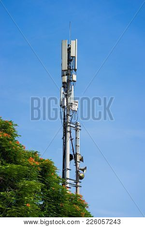 Cellular Phone Antena With Blue Sky And Green Tree Background