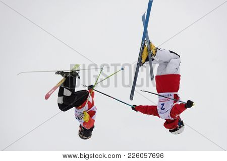 KRASNOE OZERO, LENINGRAD REGION, RUSSIA - FEBRUARY 1, 2018: Dmitry Kolesnikov (2) and Andrey Uglovski, both of Russia, compete in dual mogul during Freestyle Europa Cup competitions