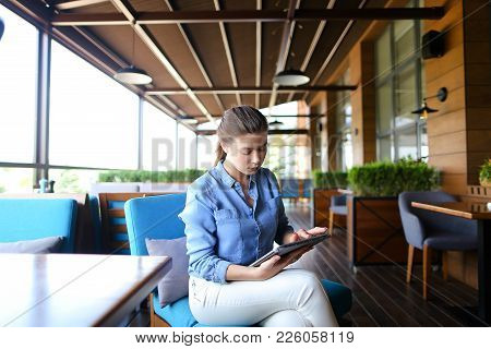 Young Girl Using Tablet At Restaurant And Sitting On Blue Sofa. Beautiful Girl Wears In Casual And H