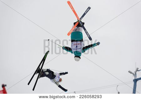 KRASNOE OZERO, LENINGRAD REGION, RUSSIA - FEBRUARY 1, 2018: Michail Dolmatov (7) and Nikita Novitckii, both of Russia, compete in dual mogul during Freestyle Europa Cup competitions