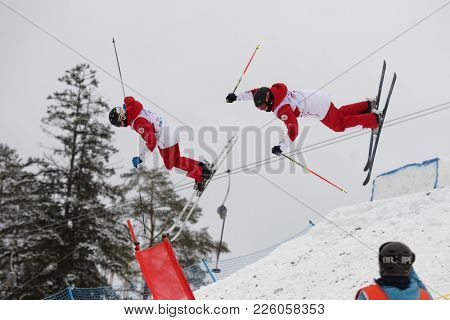 KRASNOE OZERO, LENINGRAD REGION, RUSSIA - FEBRUARY 1, 2018: Nikita Parkachev (in front) and Ilya Chevskiy, both of Russia, compete in dual mogul during Freestyle Europa Cup competitions