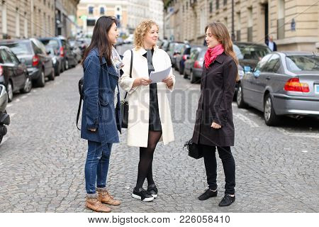 Chinese International Student Speaking With Teacher Outside In  . Concept Of Studying Abroad And Lea