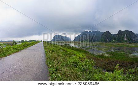 Heavy Rain Clouds Drift Across Van Long Lagoon And Dike, Ninh Binh, Vietnam