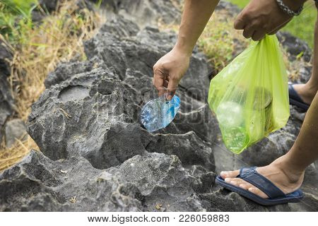 Man Hands Picking Up Litters On Rock At Tourism Place