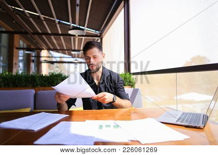 Placeman Sorting Papers On Desk Near Laptop. Strong Male Hands With Watch Near Window. Concept Of St
