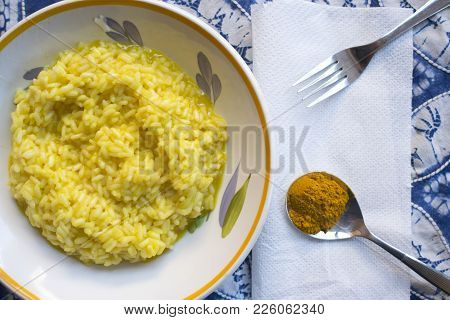 Flat Lay Of A Dish Of Saffron Rice With A Spoon Of The Principal Ingredient