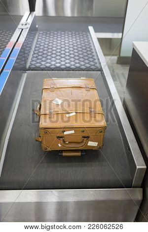 Big Leather Suitcase At Check-in Desk At Airport