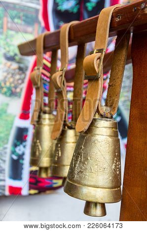 Belts With Bells Of Different Sizes For Cows. Souvenir Bells. Objects Hang On A Wooden Beam.