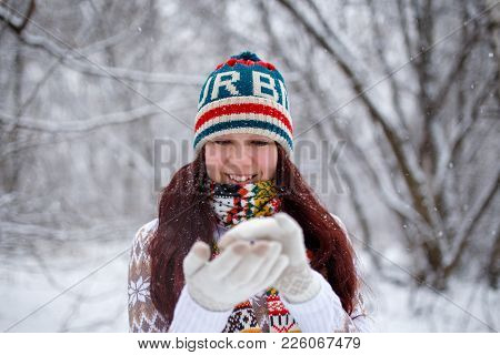 Photo Of Smiling Woman In Knitted Cap And Scarf Catching Snowflakes In Winter Forest During Day, Def