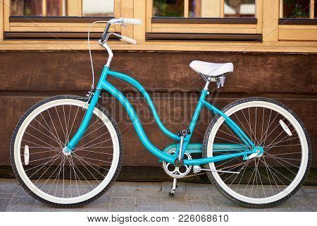 Horizontal Shot Of A Blue City Bicycle Placed Near The Wall Of A Building On The City Street Active