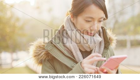 Woman use of smart phone under sunset time