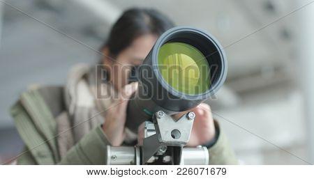 Woman looking through telescope to observe the bird habitat