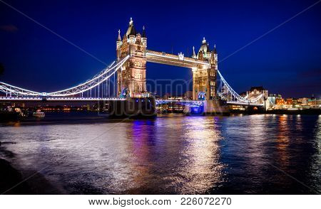 London cityscape with illuminated Tower Bridge over the River Thames at night