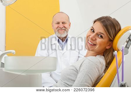 Smiling Young Woman At The Dentist With Doctor In Background, Dental Checkup
