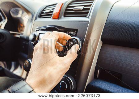 Man Turning Button Of Radio In Car